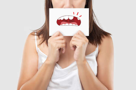 Asian woman in the red shirt holding a brown paper with the broken tooth cartoon picture of his mouth against the gray background, Decayed tooth, The concept with healthcare gums and teeth 版權商用圖片
