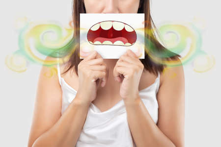 A woman wearing white dress holding a white paper with an open mouth cartoon image. On a light gray background. Bad breath or Halitosis. The concept with healthcare gums and teeth 版權商用圖片