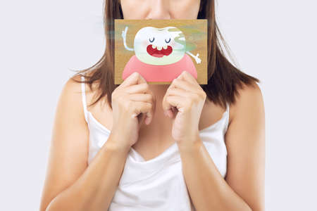 A woman wearing a white dress holding a white paper with an open mouth cartoon image. On a light gray background. Bad breath or Halitosis. The concept with healthcare gums and teeth