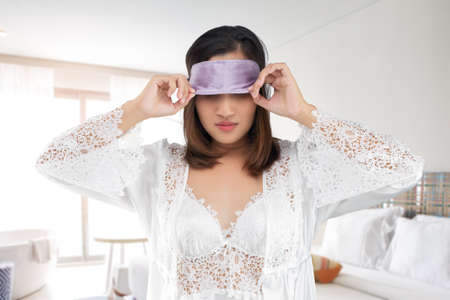 Asian woman in a lace nightgown and white satin robe take off a sleeping mask or eye mask after waking up in the morning