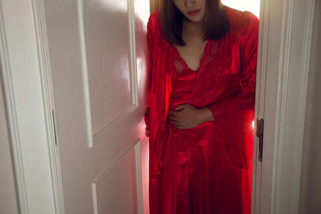 Women have a stomach ache because of diarrhea in the middle of the night. The woman in red nightgown wearing a silk robe wakes up to go to the restroom. The concept with symptoms of bowel problems