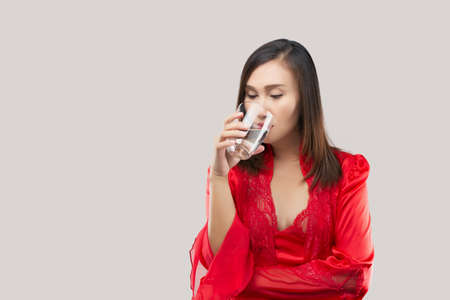 Sexy girl drinking a glass of water before bed on a gray background. Asian woman wearing red satin nightgown and lace robe drinking glass of water at night.