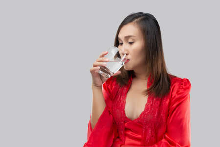 Thai Woman drinking a glass of water before bed on a gray background. Asian woman wearing red satin nightgown and lace robe drinking glass of water at night.