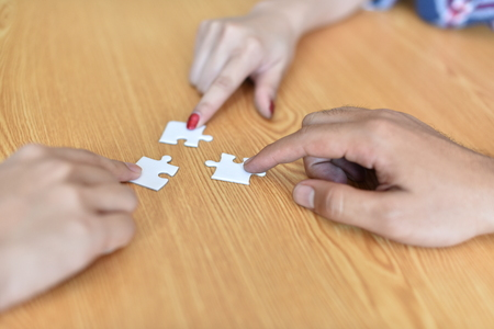 Close up of hand placing the last jigsaw puzzle piece, Hand holding missing conceptual of problem solving, finding a solution.Collaboration and business exchanges, cash, brain, dedicated team manageme Stock Photo