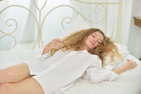 Beautiful woman in white pajamas. Stand looking and smiling. By the window in the morning.