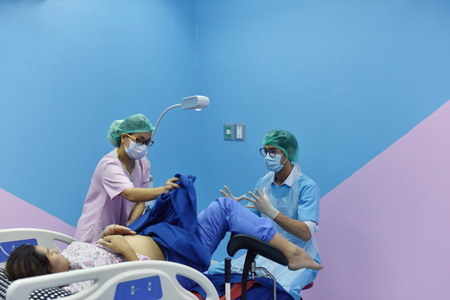 Pregnant woman assisted by a doctor and nurse in a delivery room. Medical team examining pregnant woman during delivery while man holding her hand in operating room