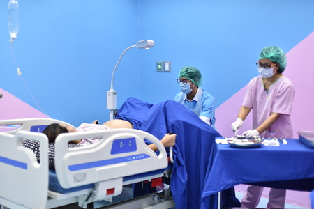 Pregnant woman assisted by a doctor and nurse in a delivery room Stock Photo