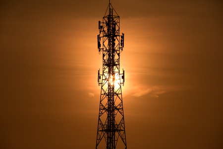 Wireless Communication Antenna With sunrise bright sky.Telecommunication tower with antennas with orange sky. Stockfoto