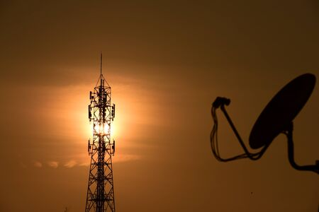 Wireless Communication Antenna With sunrise bright sky.Telecommunication tower with antennas with orange sky. Banco de Imagens