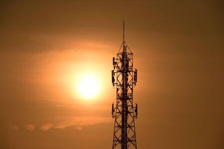 Wireless Communication Antenna With sunrise bright sky.Telecommunication tower with antennas with orange sky. Stock Photo