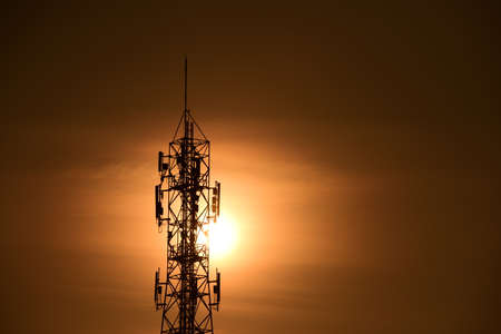 Wireless Communication Antenna With sunrise bright sky.Telecommunication tower with antennas with orange sky. Stock Photo