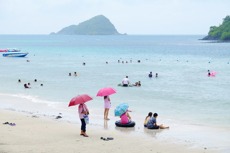 The tourists are swimming at the beach. And stroll along the sandy beach. Must use the umbrella on a rainy day at the beach, Sattahip, Chonburi, Thailand on April 28, 2018.