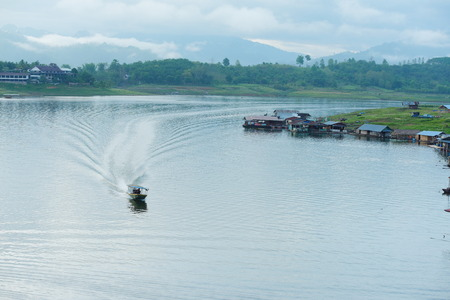 View of the river and surrounding communities of the dam near the Mon Bridge. Water in the dams and boats, villagers and community residences at Khao Laem Dam, Thailand. Stock Photo