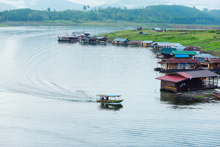 View of the river and surrounding communities of the dam near the Mon Bridge. Water in the dams and boats, villagers and community residences at Khao Laem Dam, Thailand. Editorial