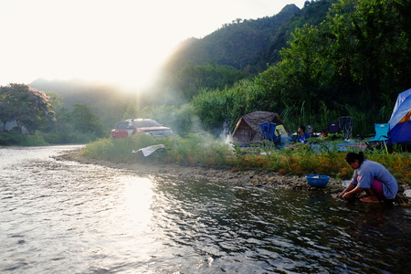 May 6, 2018,Sangkhlaburi, Kanchanaburi, Thailand: A family camping at the campsite near the stream in the rainforest