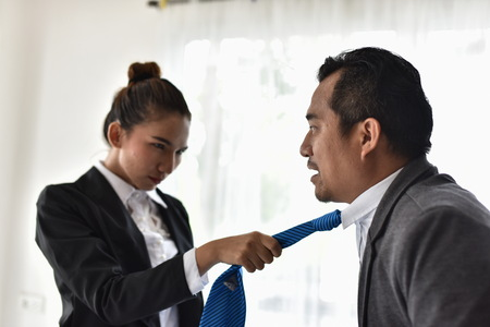 Conflict in the workplace Female employees are pulling the tie of male employees. Express anger and use force Фото со стока