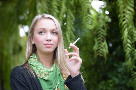 Portrait of a beautiful young woman smoking cigarettes.Health Hazards.