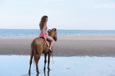 Beautiful model with beautiful horse at the beach in the evening. Before sunset 免版税图像
