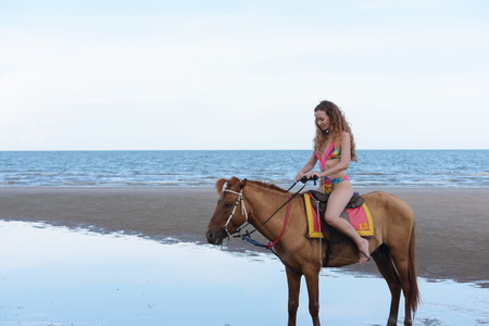 Beautiful model with beautiful horse at the beach in the evening. Before sunset Stok Fotoğraf
