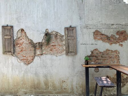 Orange brick with cracks old style on cement walls with green leave, abstract art background and vintage wallpaper