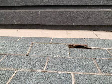 Gray tiles with cracks, floor collapses, cracked house problems Reklamní fotografie