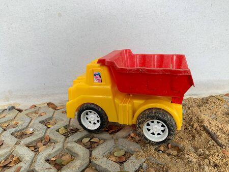 Yellow plastic childrens car On cement floor and sand Reklamní fotografie