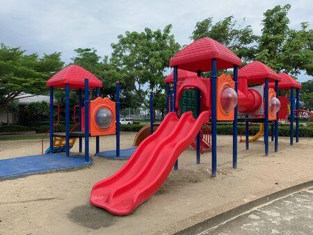 A Red child slider on the sand in the health garden, playground Reklamní fotografie