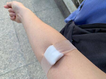 white gauze closed on arm, blood donation