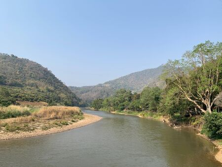The beautiful view of the river parallel to the mountains under the blue sky