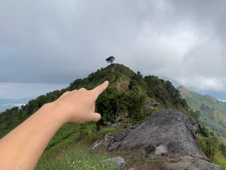 The finger pointing to the top of the mountain indicates the destination that want to reach 免版税图像