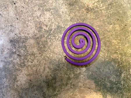 Purple mosquito coil on the cement floor