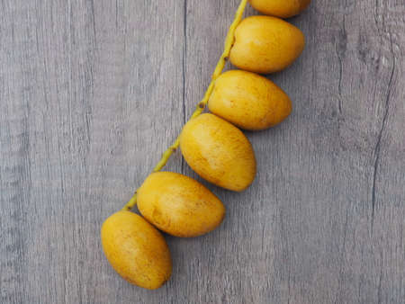 A bouquet of fresh barhee dates palm on the wooden background
