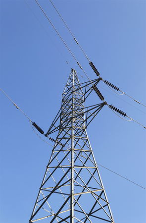 necessity: Tower of high-voltage lines with blue sky background.