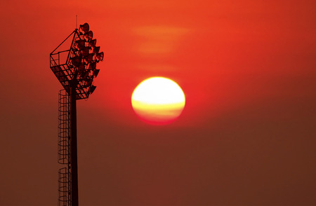 Silhouetted of old stadium lights on blurred big sunrise background.