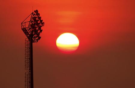 sun energy: Silhouetted of old stadium lights on blurred big sunrise background.