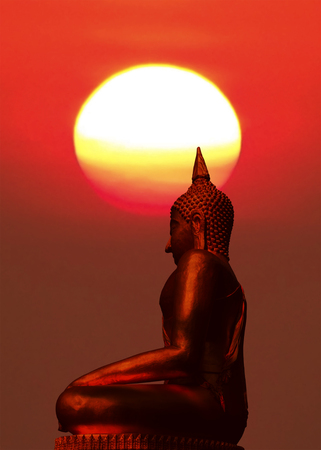 Silhouette of buddha statue with blurred sunrise background.