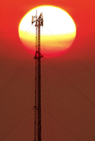 Antenna and cellular tower on blurred big colorful sun background. Stock Photo