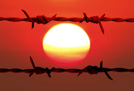 drawback: Silhouettes old barbed wire with blurry colorful of sun and sky background.