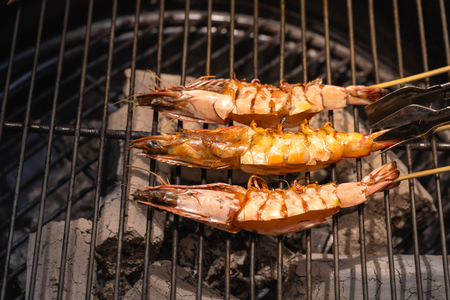 Grilled shrimp or easy BBQ grilled shrimp on grill. Grilled shrimps on the flaming grill. Diet or cooking concept.