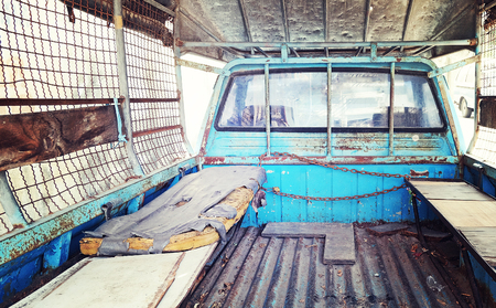 camioneta pick up: Old mattress place behind back of blue pickup truck in vintage retro style color