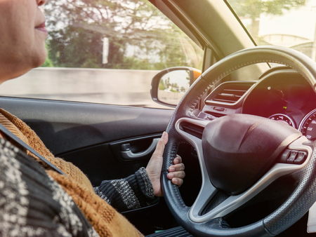 Middle-aged woman One-handed steering wheel while driving Stock Photo