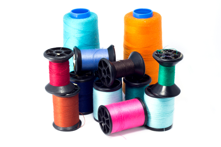 Colorful bobbins of thread isolated on white photo