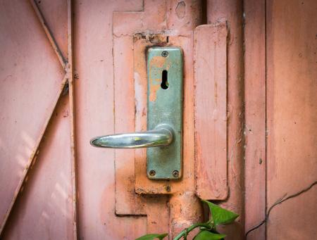 Aluminum door knob on the old door photo