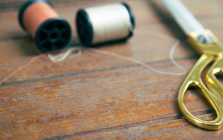 A gold scissors and spool of thread on wooden table (shallow focus) Stock Photo
