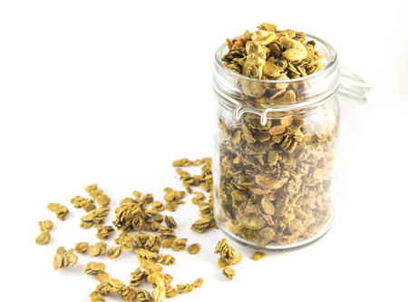 processed grains: Healthy breakfast. Fresh granola, muesli in a glass jar. Organic oat,almond and sunflower seeds isolated (focus on granola in glass jar)
