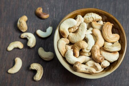 un healthy: Bowl of cashew nuts from above. On wood background. Stock Photo