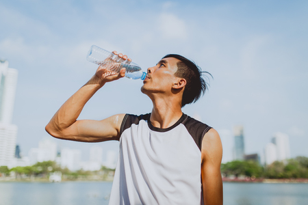 Sports man drinking water after exercising on background of public park. 版權商用圖片 - 73950187