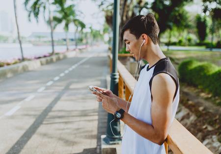 Atractivo joven deportista jugando y escuchando música de smartphone en el parque público.