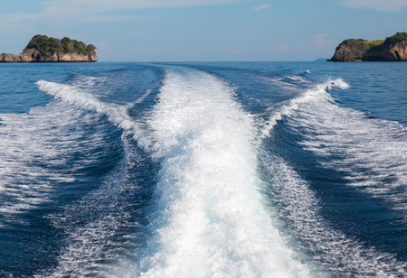 The waves from a high-speed boat and island background. Stock Photo