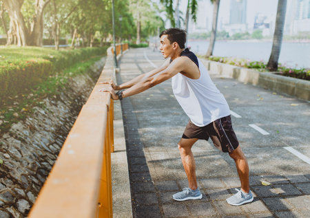 Young man stretching bodies, warming up for jogging in public park. 免版税图像